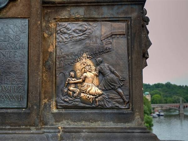 Chạm vào bức tượng thánh John xứ Napomuk cũng đảm bảo cho bạn cơ hội thăm lại Prague, thủ đô Cộng hòa Czech. Phía dưới bức tượng mô tả cảnh thánh John bị ném khỏi cây cầu.
