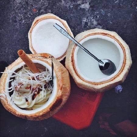 Kem dừa: Kem dừa cũng là món yêu thích khi nhắc đến ẩm thực con phố này. Bên trong quả dừa tươi, người bán khéo léo đặt vào kem tươi đã chế biến, sau đó rắc lên trên một chút dừa nạo sợi, lạc giã nhỏ, sốt chocolate và một que ốc quế. Vị kem ngọt mát, thơm mùi sữa, lạc rang giòn bùi. Bạn có thể nạo những miếng dừa béo ngậy ăn cùng. Giá của một suất kem dừa là 50.000 đồng. Ảnh: Lozi.