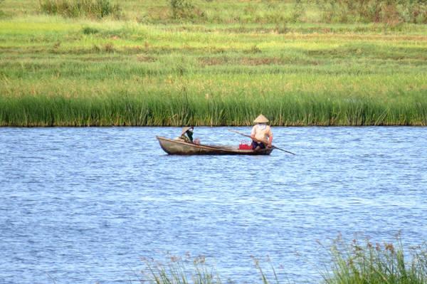 Ngư dân chèo ghe thả lưới bắt cá trên đầm - Ảnh: MINH KỲ