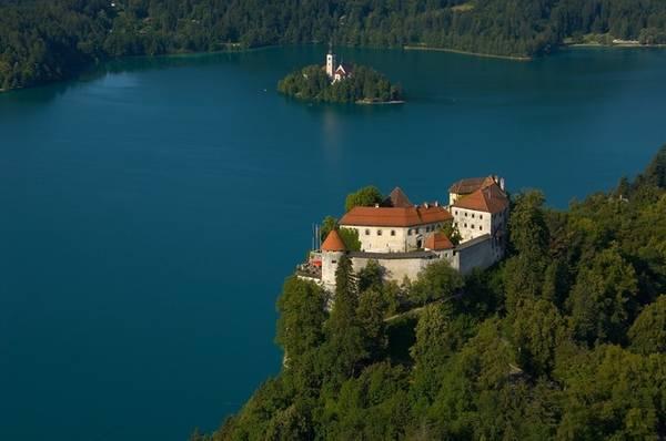 Nằm trên đỉnh một vách đá cao hơn 100 mét so với mặt hồ là tòa lâu đài Bled - biểu tượng của thành phố Bled. Hình ảnh tòa lâu đài cùng nhà thờ trên đảo đã thôi thúc rất nhiều du khách đến với đất nước Slovenia qua hàng thế kỷ. Ảnh: Bled.si