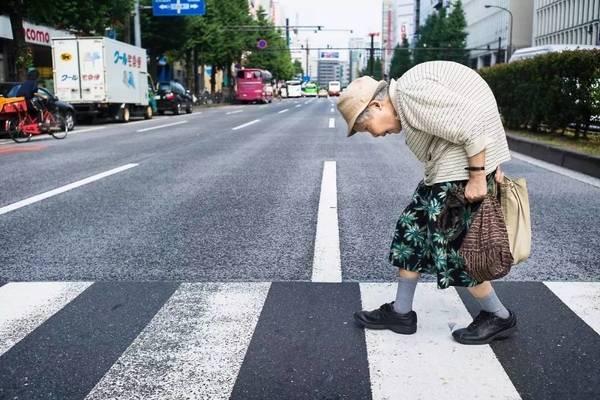 Một bà cụ còng lưng khó khăn bước qua đường.