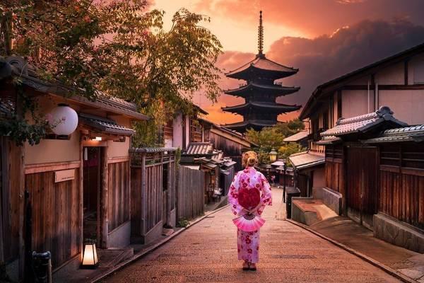 Người phụ nữ mặc kimono khoan thai dạo bước trên một con phố cổ kính ở Kyoto.