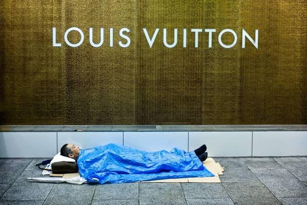 Bức ảnh người đàn ông nằm ngay ngắn dưới biển hiệu Louis Vuitton dấy lên tranh cãi liệu ông có phải là một người vô gia cư hay không.
