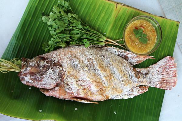 """Cá nướng sả sốt Thái: Tương tự như cá lóc nước trui của Việt Nam nhưng món ăn này lại đi kèm với một loại nước sốt đặc trưng của người Thái chua cay gồm ngò rí và các loại gia vị khác. Thật tuyệt vời khi cùng bạn bè thưởng thức món ăn này kèm những cốc bia Chang thần thánh.Địa chỉ thích hợp để ăn món này chính là Central World nhưng không phải bên trong Central World đâu nhé. Các bạn hãy đi ra ngoài Central World và hỏi người dân địa phương """"pla pao"""" nàm ở đâu,họ sẽ tận tình chỉ dẫn cho bạn,hoạc bạn cứ thấy chỗ nào gần Central World bốc khói nghi ngút thì chính xác đó là những hàng cá nướng hấp dẫn."""
