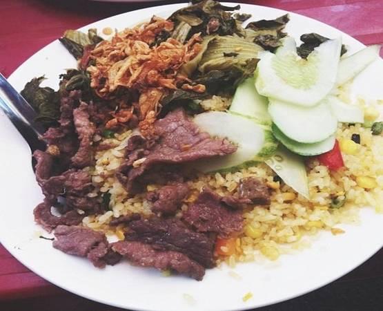 Ngõ Tràng Tiền hẹp, nằm giữa phố Nguyễn Khắc Cần và Phan Chu Trinh, tấp nập thực khách buổi trưa. Ở đây ngoài món bún đậu lòng rán, cơm rang dưa bò cũng được nhiều người yêu thích. Hạt cơm vàng ươm, đủ độ dẻo, dưa được xào vừa chín tới, lúc ăn vẫn giữ được cái giòn và chua chua đặc trưng của dưa muối, thịt bò chín vừa tới, đậm đà tạo nên sức hút của món này. Giá một phần từ 30.000 đồng. Ảnh: Giang.