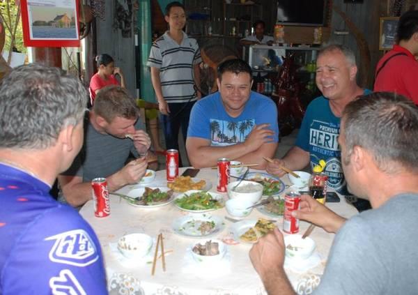 Nhóm du khách Úc phượt trên cung đường 14G bằng xe Minks đang giao lưu, ăn bữa cơm người Việt ở một ngôi nhà người Cơ Tu - Ảnh: V. HÙNG