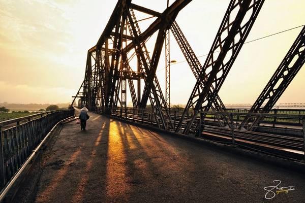 Cây cầu dưới ánh hoàng hôn. Tia nắng buông quyện với màu vàng, nâu của cầu Long Biên tạo nên khung cảnh lãng mạn trên sông.