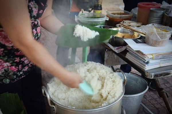 Quán xôi vỉa hè không có bàn ghế cho khách, đã bán được 50 năm, mở từ 6h đến 10h, luôn nườm nượp khách. Chủ quán chia sẻ mỗi ngày chị nấu hết 40 kg gạo, ngày chủ nhật thì ít hơn. Gạo nấu xôi phải đảm bảo độ dẻo, thơm mùi nếp.