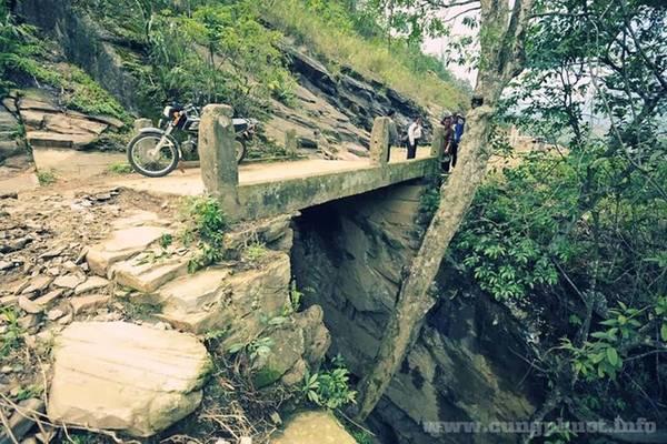 """Cầu Thiên Sinh nằm ở cuối thôn Lao Chải, cách trung tâm xã Ý Tý gần 10 km. Theo tiếng dân tộc Hà Nhì, cầu có tên là Thiên Sân Shù có nghĩa """"trời sinh"""". Cầu chỉ ngắn chừng một mét, trước đây là một tảng đá tự nhiên bắc qua khe sâu hun hút, phía dưới là dòng suối Lũng Pô. Cây cầu cũng chính là nơi nối liền Việt Nam - Trung Quốc, bước qua cầu là cột mốc 87 thuộc địa phận Trung Quốc. Ảnh: cungphuot."""