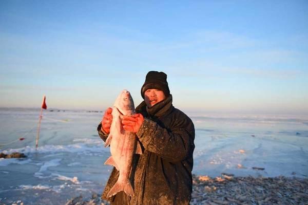 Ngư dân khoe một con cá mới câu được tại mặt hồ đóng băng Hulun (Ảnh: Xinhua)