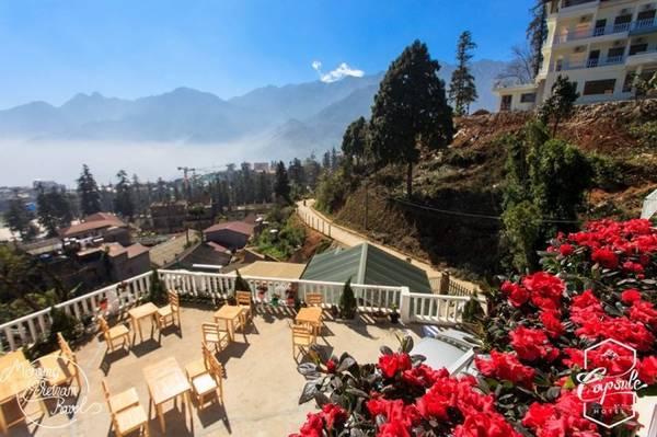 Ban công khách sạn ngập nắng và view nhìn toàn cảnh thị trấn Sa Pa bao quanh bởi những dãy núi trùng điệp.