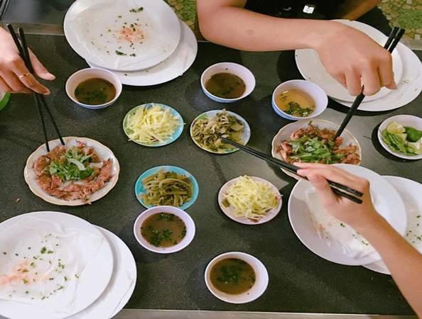 """Bánh ướt Buôn Mê Bánh ướt dạng tự cuốn khá nổi tiếng ở Buôn Mê Thuột đã có mặt ở Đà Nẵng. Bánh ướt được tráng mỏng, làm chín bằng hơi nước rồi trải ra đĩa. Thực khách sẽ tự cuốn bánh với thịt nướng, dưa leo, cải chua xắt sợi, rau thơm, đồ chua. Mắm chấm là mắm nêm hoặc mắm cá cơm. Nhiều người gọi vui đây là món bánh ướt """"chồng đĩa"""" vì ăn đến đâu sẽ chồng đĩa không đến đó. Một phần cơ bản gồm một đĩa thịt nướng, bánh ướt, giá 30.000 đồng. Bạn có thể ăn ở quán trên đường Lê Đình Dương, quận Hải Châu."""
