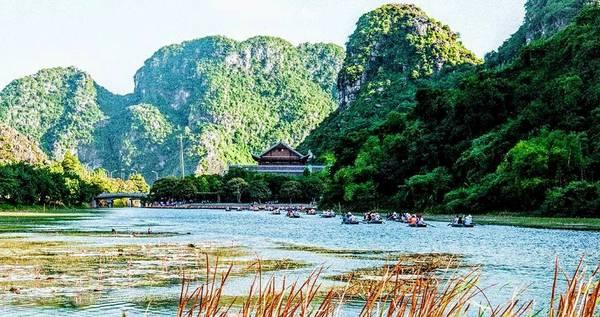 Tràng An là khu du lịch nổi tiếng nhất của Ninh Bình hiện nay. Với phong cảnh thiên nhiên hoang sơ, tuyệt đẹp, vào tháng 6/2014, Tràng An được UNESCO công nhận là di sản thiên nhiên và di sản văn hóa thế giới. Khung cảnh nơi đây được tạo nên từ dòng sông chạy uốn lượn qua các dãy núi đá vôi, tạo thành vô vàn những hang động tự nhiên huyền ảo, kỳ bí. Ảnh: Bùi Trường Chung.