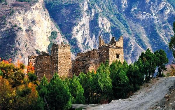 Một ngôi nhà đổ nát, cổ kính nằm giữa những triền núi.