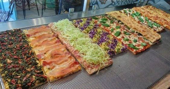 """Được phát minh ở Rome, pizza al Taglio (nghĩa đen là """"bằng cách cắt"""") cho phép bạn mua một miếng bánh pizza hình vuông yêu thích theo cân nặng."""