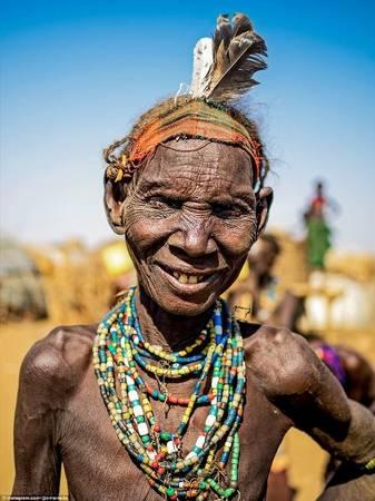 """Một phụ nữ khác của bộ tộc Dassanech nổi bật với những lớp vòng đeo cổ sặc sỡ. Người đeo trên đầu những chiếc lông chim đà điểu là dấu hiệu họ đã giết một con vật hoang dã hoặc một kẻ thù của bộ tộc. Chia sẻ về dự án nhiếp ảnh độc đáo của mình và chuyến đi được tiếp đón nồng nhiệt bởi các bộ tộc ở Ethiopia, Omar nói: """"Tôi mong muốn có thể giới thiệu vẻ đẹp đa dạng của các nền văn hóa trên thế giới""""."""