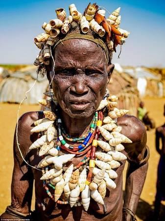 """Bộ vòng và """"vương miện"""" bằng vỏ sò độc đáo này được xem như những thứ trang sức rất được yêu thích trong bộ tộc Dassanech. Người dân bộ tộc này chuyển địa điểm sống vài tháng một lần nhưng vẫn nằm ở khu vực dọc sông Omo."""