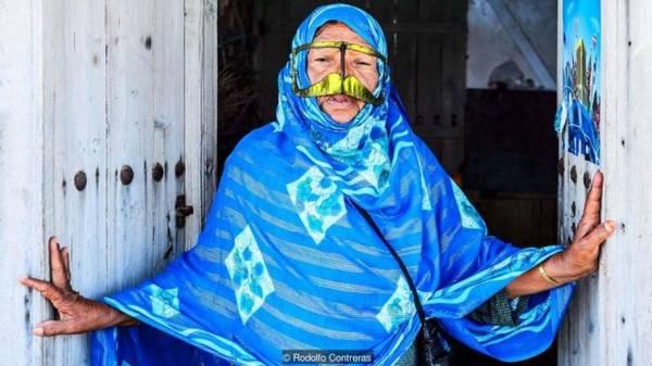 Chiếc mặt nạ của chiến tranh Chiếc mặt nạ hình ria mép lạ lùng trong ảnh là của những phụ nữ ở đảo Qeshm. Chúng được cho rằng có thiết kế từ hàng thế kỷ trước để khiến phụ nữ địa phương trông cứng rắn và dữ dằn hơn. Hòn đảo Qeshm có vị trí chiến lược nên rất dễ bị xâm lược, khi kẻ thù nhìn thấy phụ nữ đeo mặt nạ họ sẽ lầm tưởng là các binh lính nam giới.