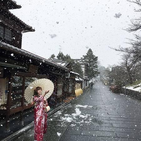 Thiếu nữ Nhật Bản xinh đẹp trong trang phục kimono khẽ khàng vươn tay hứng lấy những bông tuyết trắng, khiến cảnh sắc mùa đông như bớt đi cái lạnh giá