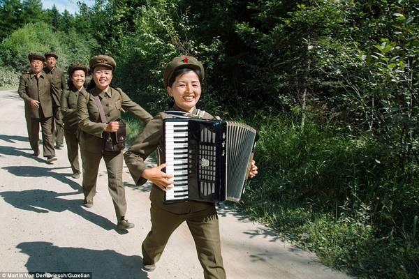 Một nhóm lính mặc đồng phục chơi nhạc trong lúc diễu hành qua vùng nông thôn ở Triều Tiên