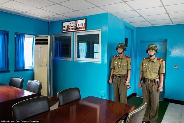 Hai người lính Quân đội Nhân dân Triều Tiên (KPA) đứng gác trong một phòng họp tại Khu vực An ninh Chung (JSA), phía trước cánh cửa dẫn sang Hàn Quốc.
