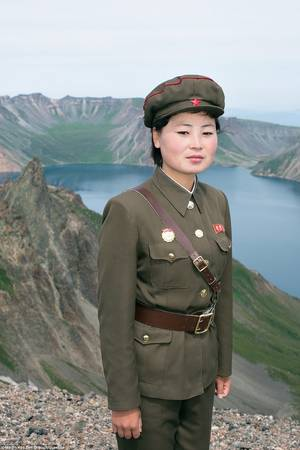 """Một người lính đứng trên núi thánh Paektusan, phía sau là hồ Chon, hay còn gọi là """"Hồ Thiên Đường"""", với những vách đá bao quanh."""