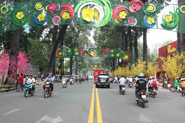 Đường Phạm Ngọc Thạch, phía trước Nhà văn hoá Thanh niên TP.HCM, được trang trí rực rỡ với một bên hàng cây hoa đào, một bên mai vàng, thu hút rất đông người dân đến chụp ảnh.