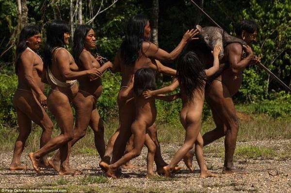 Người đàn ông được phụ nữ và trẻ con trong làng đón mừng sau khi trở về từ buổi đi săn với chiến lợi phẩm là một con heo rừng