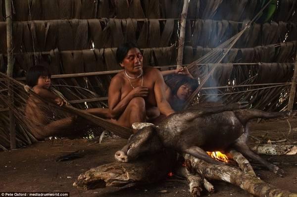 Trẻ em nằm võng nhìn người lớn nướng thịt heo rừng trên bếp lửa
