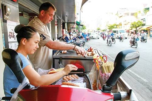 Xúc xích ông Tây Khách quen vẫn thường gọi xe xích xúc vỉa hè đường Dương Bá Trạc, quận 8 của vợ chồng anh Cliford Alexander Van Toor (người Hà Lan) và chị Trinh là xúc xích ông Tây. Mọi đồ nghề đều được đặt trên yên chiếc xe máy. Các loại xúc xích ở đây khá đa dạng với các loại bò, gà, heo và nhân phô mai, được nhập từ Đức nên chất lượng được thực khách đánh giá cao. Xúc xích nướng trên than hoa, ăn không hoặc ăn kèm bánh mì, giá từ 25.000 đồng. Ảnh: Thành Hoa.