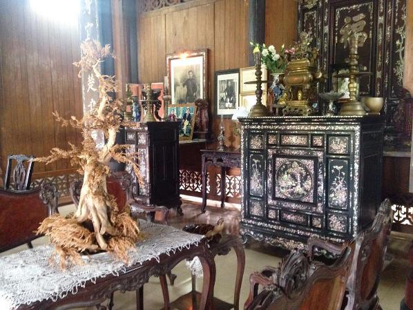 Gian trước trang trí đồ cổ bắt mắt, những tủ thờ cẩn xà cừ, chiếc hộp gỗ cẩn hình rồng, bộ liễn cẩn ốc xà cừ càng tô điểm thêm vẻ cổ kính của ngôi nhà. Ảnh: chelseatrekking.