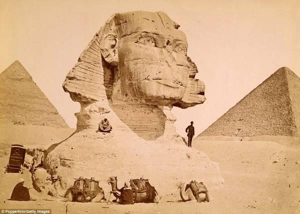 Một nam du khách đứng trên vai bức tượng nhân sư ở Giza năm 1890. Bên trái là kim tự tháp Kephren và bên phải là kim tự tháp Kheops. Ảnh: Pepperfoto/Getty.