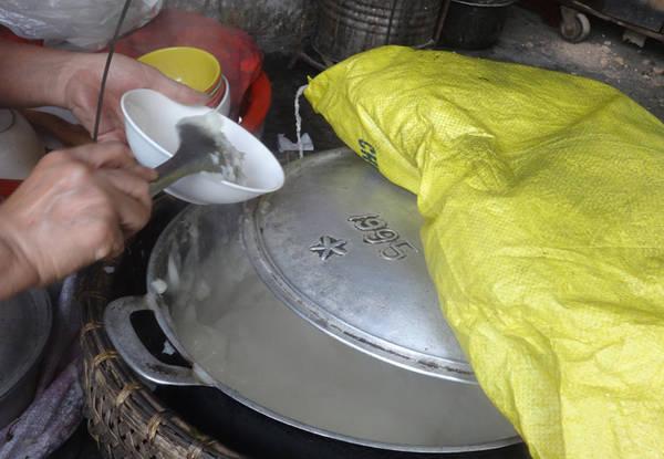 Nồi bánh đúc nghi ngút khói, được ủ ấm xung quanh bằng vải bông lèn chặt. Có khách, cô Hạnh chỉ mở hé vung nồi đang nghi ngút khói, múc bánh thật nhanh rồi đậy ngay vào cho ấm. Bánh đúc ở đây mềm, không quánh đặc như các quán khác nhưng rất dễ ăn và dễ xúc. Ảnh: Tuyết Mai.
