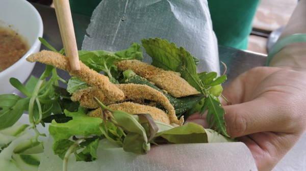 Xếp các loại rau lên bánh tráng, bỏ gỏi cá lên trên và cuộn lại, chấm ngập trong chén nước chấm, bụng đã no căng mà vẫn còn thòm thèm - Ảnh: Thanh Ly
