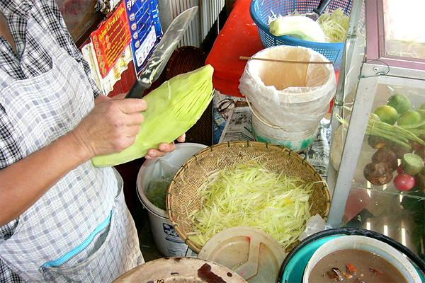 Người Thái băm đu đủ và gọt sợi để làm món som tam.