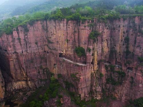 """Muốn tới Guoliang, du khách phải vượt qua một con đường chật hẹp và trơn trượt bên vách đá dựng đứng, cheo leo ở độ cao 1.752 mét. Vì lẽ đó, Guoliang còn được mệnh danh là """"ngôi làng trên mây"""", hay """"ngôi làng trên 9 tầng trời"""". Ảnh: Cultural China."""