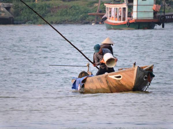 Đổ hến vào ghe để vận chuyển vào bờ - Ảnh: THANH LY
