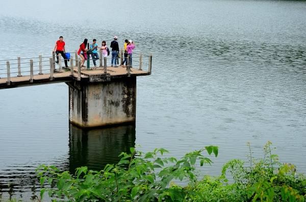 Các bạn trẻ đứng trên van lấy nước vào cánh đồng để ngắm toàn cảnh hồ.