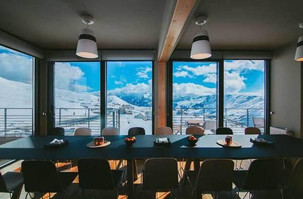 Nhà hàng với cửa kính lớn nhìn ra mây trời bao la và núi tuyết trắng xóa.