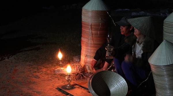 Người bán dùng ánh sáng đèn dầu đỏ và ấm nên không bị lóa, người mua soi rõ được những đường kim, mũi cước trên từng chiếc nón.