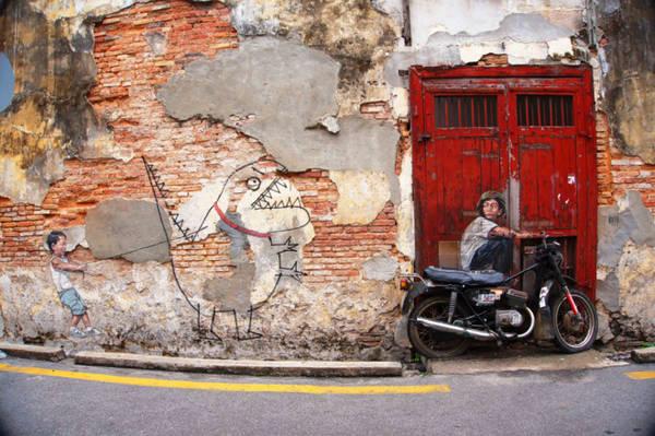 Tranh tường chú bé ngồi trên xe máy.