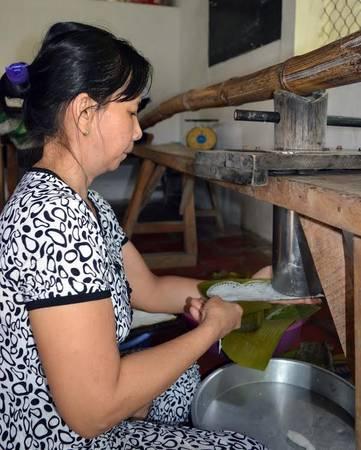 Để tạo được bánh hỏi hình mặt võng người thợ phải hứng lá chuối dưới khuôn đổ bánh hình trụ và kết hợp thao tác tay khéo léo.
