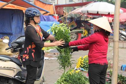 """Cô Nguyễn Thị Oanh (phố Định Công, Q.Hoàng Mai) chia sẻ: """"Cứ độ tháng tư này, tôi thường chọn hoa loa kèn vì hoa này bền, để được lâu, lại thơm dịu dàng""""."""