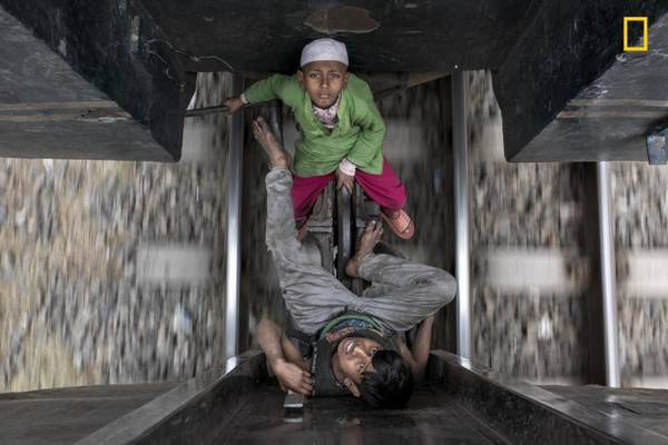 Hai anh em Taj và Akash (Bangladesh) mỗi ngày 'nhảy tàu' từ ga này đến ga kia để xin tiền. Dù nguy hiểm và bất hợp pháp, nhiều người Bangladesh vẫn coi 'nhảy tàu' là cách di chuyển thông thường của mình - Ảnh: Mauro De Bettio