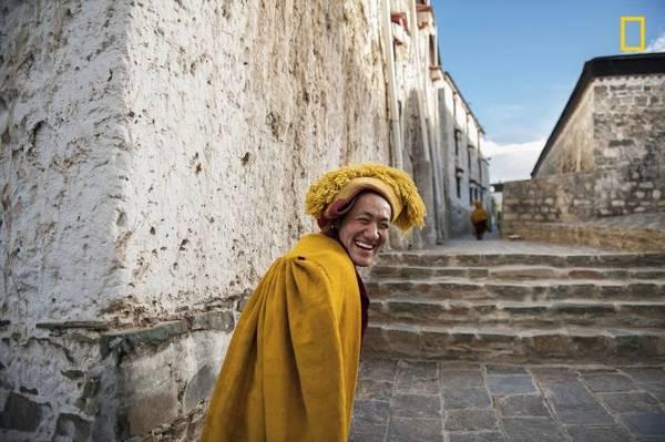 """Ảnh chụp tại Tu viện Tashi Lhunpo ở Tây Tạng. """"Vị sư phụ này đang trở về phòng mình sau buổi cầu nguyện chiều. Tôi đã đuổi theo ông ấy để chụp ảnh, nhưng ông che mặt. Đột nhiên ông ấy quay đầu lại và cười vang"""", nhiếp ảnh gia Mattia Passarini chia sẻ - Ảnh: Mattia Passarini"""