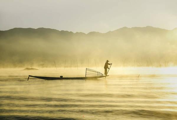 Ngư dân đánh bắt cá khi hơi sương bốc hơi lên từ mặt hồ. Ánh ban mai làm quang cảnh hồ đẹp như bức tranh thủy mặc.