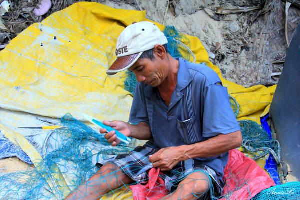 Một ngư dân đang chăm chú vá lưới cho kịp buổi đánh cá đêm.