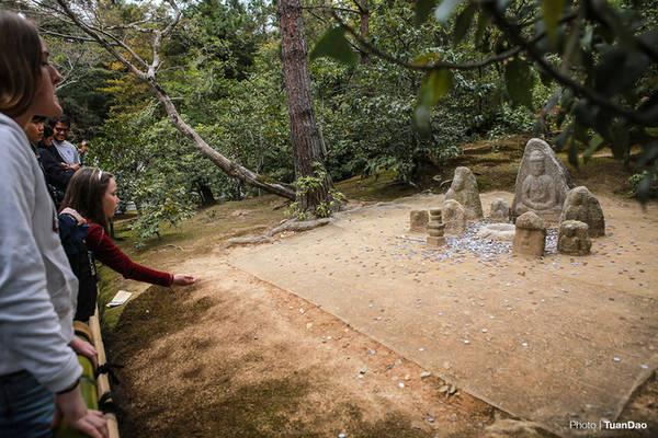 Du khách ném tiền xu cầu may trong khuôn viên chùa.