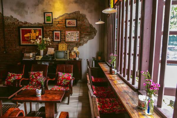 """Tổ hợp với tầng một là quán café xinh xắn theo phong cách bao cấp, khiến nhiều người thích thú khi hoài niệm lại ngày xưa, với đệm và gối họa tiết con công, bộ bàn ghế mà """"ngày xưa nhà nào cũng có""""."""