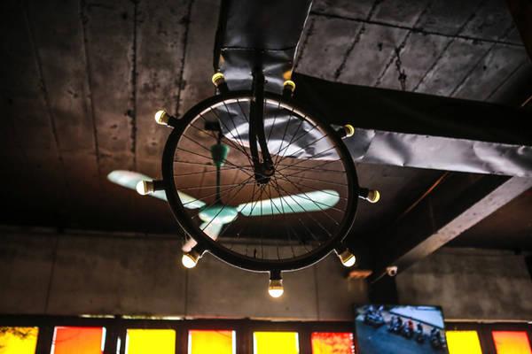 Ở đây bạn còn thấy sự phá cách trong trang trí với bánh xe đạp được biến thành đèn trần nhà độc đáo.